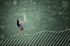 Female student carrying books on blackboard Stock Photos