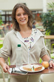 Female student carrying food tray in the cafeteria Stock Photography