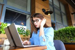 Student chatting by laptop with friends at cafe. Female student chatting with friends by laptop at cafe. Young girl dressed in jeans shirt sitting near window stock images