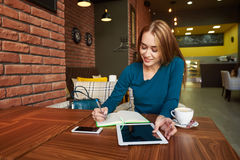 Female student is checking e-mail on digital tablet. While  writing in a notebook Businesswoman is ordering on-line car via touch pad, while is sitting in cafe Royalty Free Stock Image