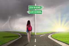 Female student with choices to stay or leave school. Picture of a female high school student walking on the road with two choices to stay or leave school stock images