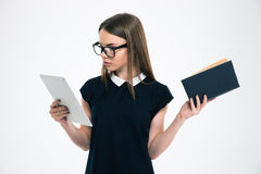 Female student choosing between tablet computer and book Royalty Free Stock Photos