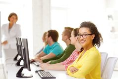 Female student with classmates in computer class. Education, technology and school concept - smiling male student with classmates in computer class with teacher Stock Photo