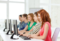 Female student with classmates in computer class. Education, technology and school concept - smiling female student with classmates in computer class at school Royalty Free Stock Photo