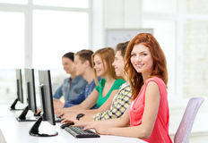 Female student with classmates in computer class. Education, technology and school concept - smiling female student with classmates in computer class at school Royalty Free Stock Image