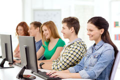 Female student with classmates in computer class. Education, technology and school concept - smiling female student with classmates in computer class at school Royalty Free Stock Photography