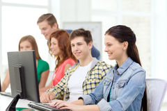Female student with classmates in computer class. Education, technology and school concept - smiling female student with classmates in computer class at school Stock Image