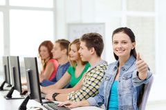 Female student with classmates in computer class. Education, technology and school concept - smiling female student with classmates in computer class at school Royalty Free Stock Images