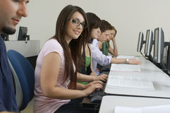 Female Student With Classmates In Computer Lab. Portrait of young female student typing while sitting among classmates in computer lab Stock Photos