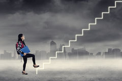Female student climbing the stair Stock Photo