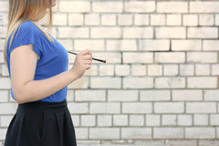 Female student concept. Beautiful girl. Near a brick wall. Write with a brush in profile. Photo for your design Stock Photos