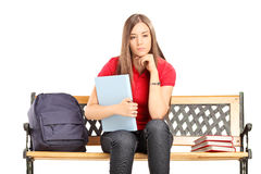 Female student contemplating seated on a bench Stock Photography