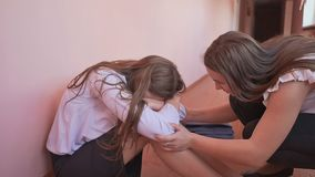 A female student is crying on the floor of a corridor at school. The friend approaches and calms the schoolmate. A female student is crying on the floor of a stock video footage
