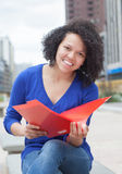 Female student with curly hair looking at camera in the city Stock Photography
