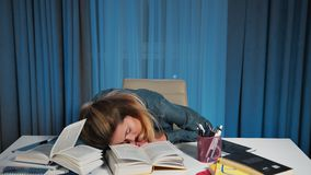 A female student in a denim shirt, tired and fell asleep on a table with books. stock footage