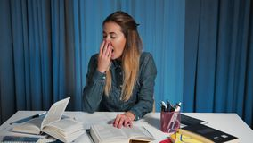 A female student in a denim shirt, yawns from fatigue. A boring homework. stock video footage