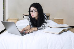 Female student doing homework on the bed Royalty Free Stock Images