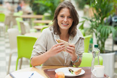 Female student eating sandwich in the cafeteria. Portrait of a smiling female student eating sandwich in the cafeteria Stock Photography