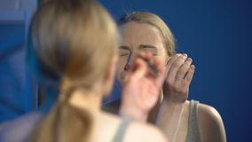 Female student feeling pain while plucking eyebrow with tweezers, beauty routine. Stock footage stock video