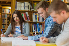 Female student with friends at library desk Royalty Free Stock Photos