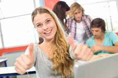 Female student gesturing thumbs up in classroom. Portrait of happy female student gesturing thumbs up in classroom Royalty Free Stock Photography