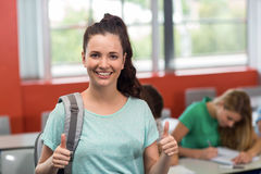 Female student gesturing thumbs up in classroom Stock Photos