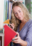 Female student getting books in a library Stock Photography