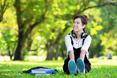 Female student girl outside in park listening to music on headphones while studying