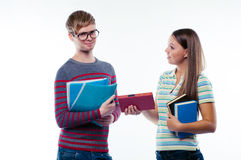 Female student giving a book to male student Stock Photo