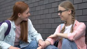Female student giving helping hand to bullied nerd girl, supportive friend