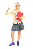 Female student giving a thumb up and holding notebooks Stock Image