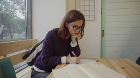 Female student in glasses sitting at table and studying stock footage