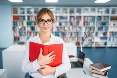 Female student in glasses, university library. Pretty female student in glasses with opened book in university library. Young woman in reading room, knowledge royalty free stock image