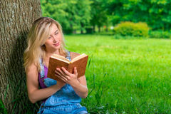 Female student with a good book in the park Royalty Free Stock Image