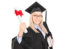 Female student in graduation gown holding books and a diploma Stock Photography
