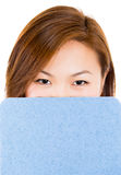 Female student hiding face behind clipboard Royalty Free Stock Photo