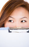 Female student hiding face behind clipboard Royalty Free Stock Image