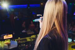 The female student is holding the black wireless microphone in the left hand and do the public speaking with blurred. Background royalty free stock photography