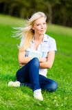 Female student holding book sits on the green grass Stock Photos