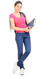 Female student holding books and leaning on a wall Royalty Free Stock Images