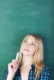 Female Student Holding Chalk While Looking Up Against Chalkboard Royalty Free Stock Image