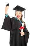 Female student holding diploma and taking selfie Stock Photo