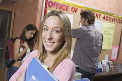 Female Student Holding Folder. Portrait of a happy female student in college office clutching folder Royalty Free Stock Photo