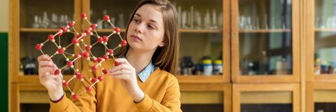 Female student holding molecular structure model. Science class concept. royalty free stock photography
