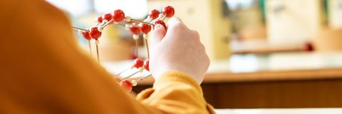 Female student holding molecular structure model. Science class concept web banner. royalty free stock photography
