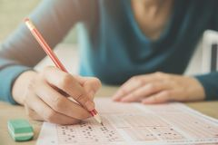 Female student holding pencil and examination paper stock images
