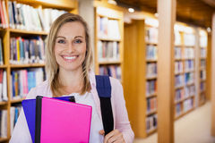 Female student holding textbooks in the library Royalty Free Stock Photography