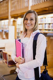 Female student holding textbooks in the library stock images