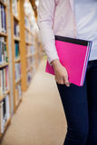 Female student holding textbooks in the library Royalty Free Stock Images