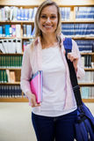 Female student holding textbooks in the library Royalty Free Stock Image